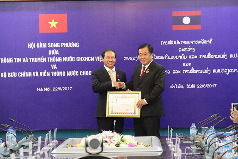 Bộ trưởng Bộ Bưu chính và Viễn thông Lào Thansamay Kommashith trao Huân chương Lao động hạng Nhì cho ông Đoàn Quang Hoan, Cục trưởng Cục Tần số Vô tuyến điện.